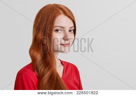 Sideways Portrait Of Freckled Serious Red Haired Female Model Looks Confidently Into Camera, Poses A