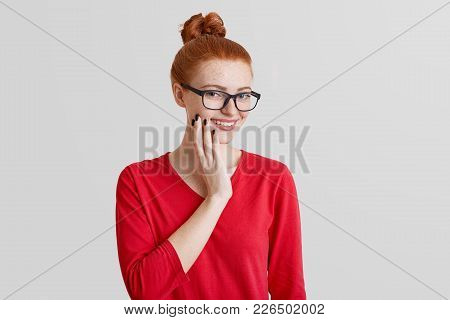 Pleased smiling freckled female with ginger hair tied in knot, wears casual clothes and eyewear, has manicure, looks with cheerful expression, poses against white background. Beauty concept. poster