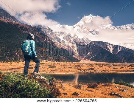 Standing Young Woman With Backpack On The Stone And Looking On Mountains In Clouds At Sunset. Landsc