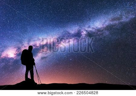 Silhouette Of Man With Backpack And Trekking Poles Against Amazing Purple Milky Way At Night. Space.