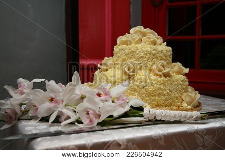 Rome, Italy - Apr 10, 2008 White Chocolate Wedding Cake On A Table , With Bridal Bouquet Beside