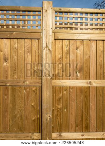 Wooden Fence Panelling With Fancy Top, Golden In Color And Sunlit