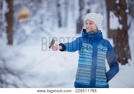 Teenager Girl Feeds A Titmouse With His Hands In The Winter Forest
