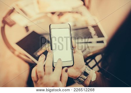 Close Up Woman Hand Using A Smart Phone In The Beauty Salon. Toned Image. Girl Looks In The Phone In