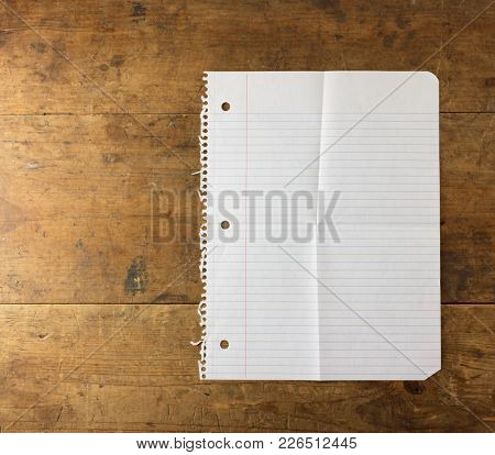 Note pad paper of spiral notebook, with fold marks, on old wooden desk. Isolated on white.
