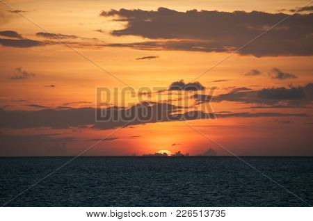 Sunset In The Maldives: The Disk Of The Star Disappeared Behind The Horizon, The Orange Glare In The