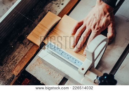 A Carpenter Works On Woodworking The Machine Tool. Toned Image. Man Collects Furniture Boxes. Saws F