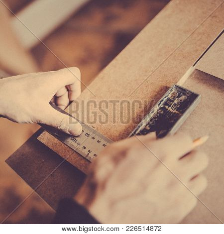 A Carpenter Uses A Framing Square For Marking A Hole In A Furniture Part. Toned Image. Puts The Poin