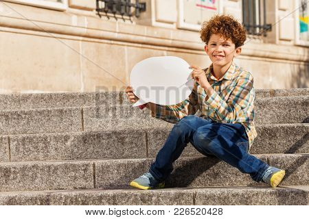 Cute Teenage Boy Sitting On The Stairs Outdoors, Holding Blanked Speech Bubble
