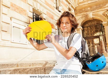 Teenage Boy Sitting On The Steps Outdoors With Yellow Blanked Speech Bubble