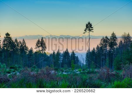 Early morning haze in the mountains with the Canadian rockies in the horizon, seen from Ladysmith, Vancouver Island BC