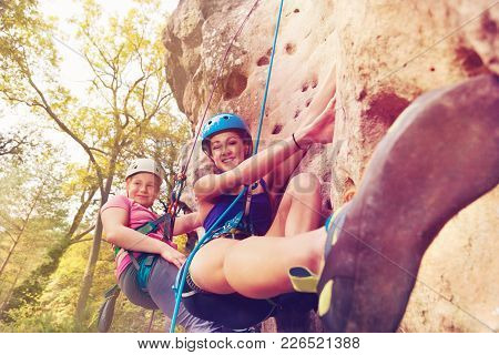 Portrait Of Female Instructor Teaching Teenage Girl Climbing A Rock With Harnesses In Forest Area