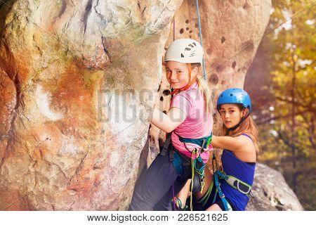 Female Instructor Of Rock Climbing With Teenage Girl Training Outdoors Wearing Helmets And Harnesses