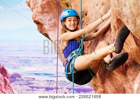 Smiling Young Woman Rock Climbing With Harness Outdoors High In The Mountains