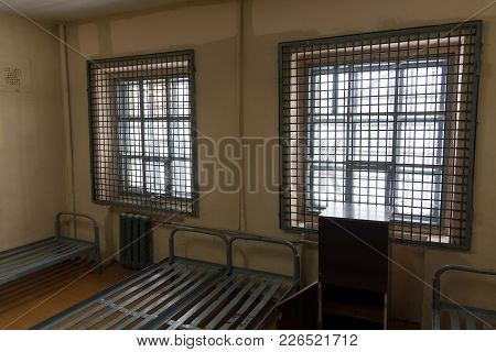 View Of The Prison Cell From The Inside. Lattices On The Windows And Iron Beds.