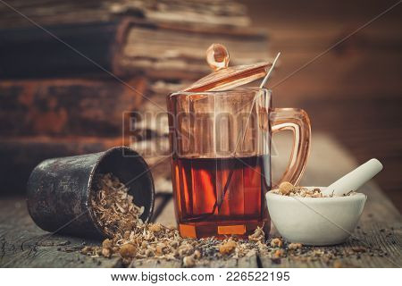 Tincture Or Healthy Tea In Glass, Mortars Of Healthy Daisy Herbs And Old Books.