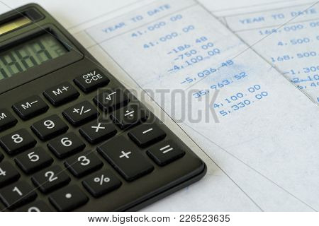 Tax Calculation Or Financial Office Salary, Black Calculator On Salary Slips With Numbers, Year To D