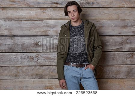 Young Model Man Posing On Wood Background Wearing A Stylish Casual Look, Holding Hand In Pocket, Put