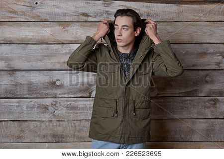 Young Model Man Posing On Wood Background Wearing A Stylish Casual Look, Putting The Hood On Head, H
