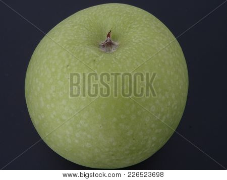 Close Up Of A Granny Smith Apple On A Black Background