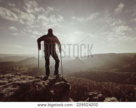 Disabled Man With Forearm Crutches On The Edge. View Over The Hilly Ladscape In Summer Evening. Hurt