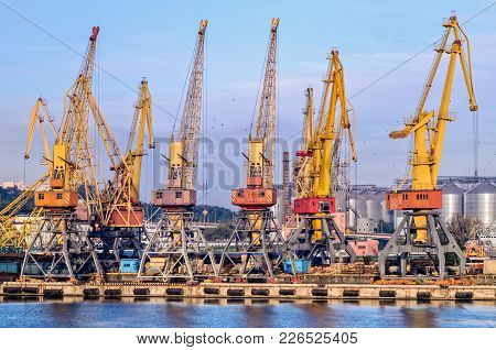 Yellow Cranes In A Seaport Against A Background Of Metal Granaries And A Blue Sky With Clouds And Fl
