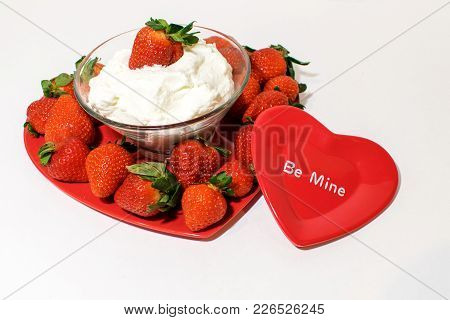 Red Heart In Front Of A Heart Shaped Tray Filled With Ripe Strawberries.