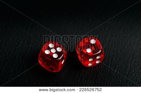 Two dice counting seven on a black leather