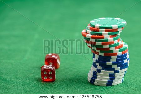 casino chips and red dice on a green felt as background