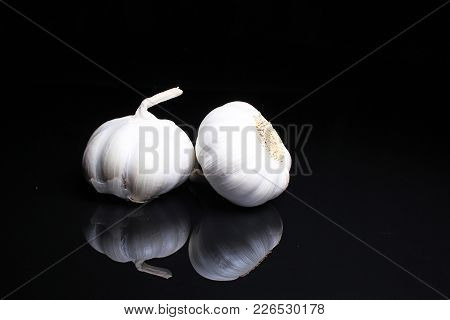 Garlic On Black Reflective Studio Background. Isolated Black Shiny Mirror Mirrored Background For Ev