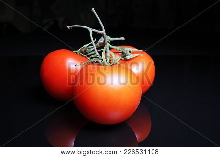 Tomato On Black Reflective Studio Background. Isolated Black Shiny Mirror Mirrored Background For Ev