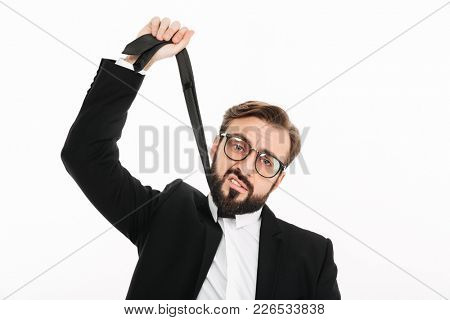 Image of tired young businessman standing isolated over white background. Looking camera displeased because of work.