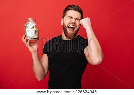 Photo of excited bearded man standing isolated over red background wall holding jar full of money make winner gesture.