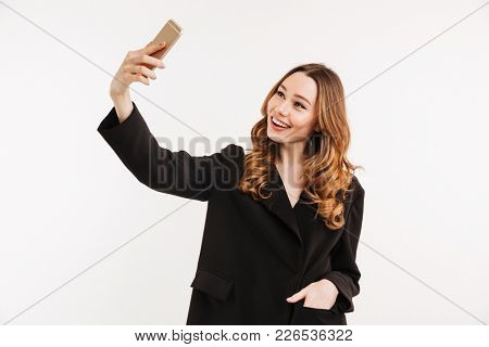 Image of sociable pretty woman in black jacket making selfie and smiling on her cell phone isolated over white background