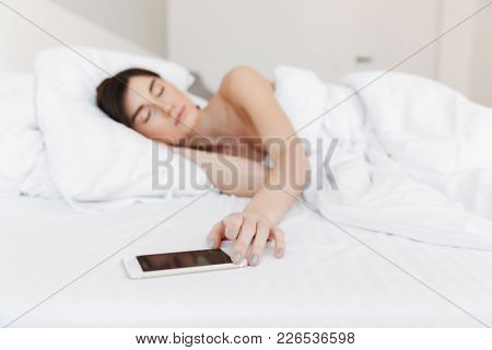 Portrait of a beautiful young woman holding hand on her phone while lying in bed at the bedroom