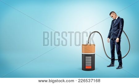 A Sad Businessman With His Head Down Stands Connected By Cable To A Large Empty Battery.