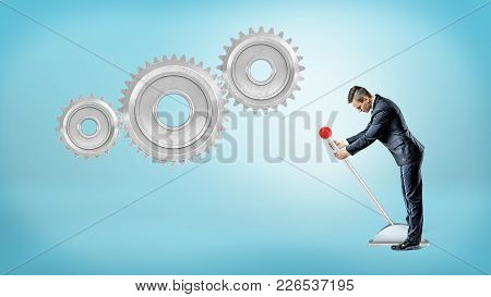 A Small Businessman Pulls A Large Lever Near Three Giant Interlocked Gears Hanging On A Blue Backgro