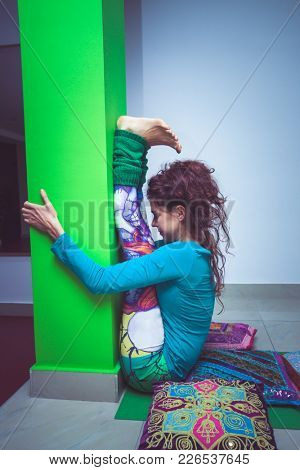 young woman practice yoga stretching against column indoor shot
