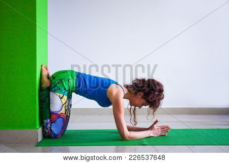 young woman in yoga position against wall indoor full body shot