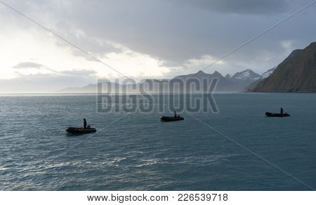 Three Drivers Navigating Zodiak Inflated Boats In The Blue Atlantic Ocean Water. Rugged Mountains Wi