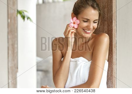 Beautiful Smiling Woman After Bath Covered By White Towel, Holds Flower As Had Aromatherapy, Looks T