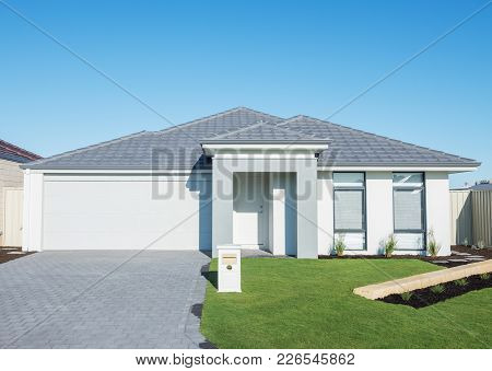 typical facade of a modern suburban house against blue sky poster