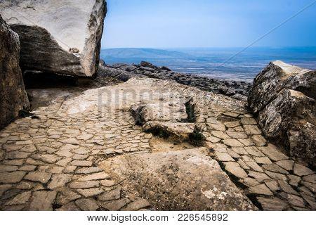 Gobustan national park ancient rocks, rock path and mountains near Baku in Azerbaijan. Exposition of Petroglyphs in Gobustan near Baku, Azerbaijan.