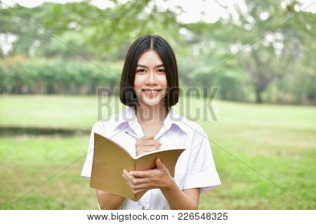 Education Concepts. Beautiful Student Reading Books In The Park. Beautiful Girl Are Relaxing In The