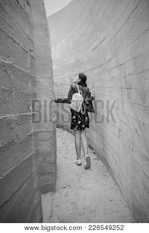Attractive Young Hipster Woman Stands Between Concrete Walls. Caucasian Fashion Girl In Casual Jeans