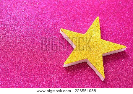 A Golden Star On A Shinny Pink Background