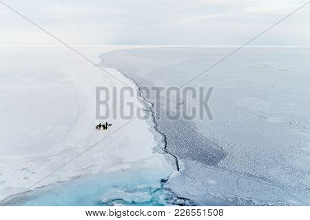 A Small Group Of Emperor Penguins Near A Crack In The Sea Ice. Ross Sea, Antarctica.