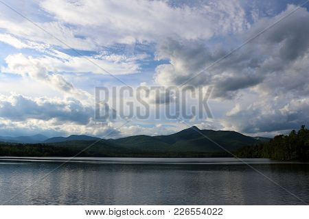 Mountains In The Distance In New Hampshire Reflected On The Water With Clouds.