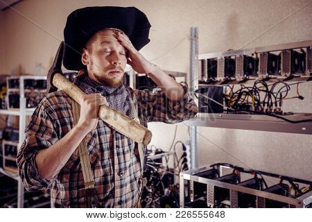 A Man Holds His Forehead With A Tool In His Hand Against The Background Of Computer Devices