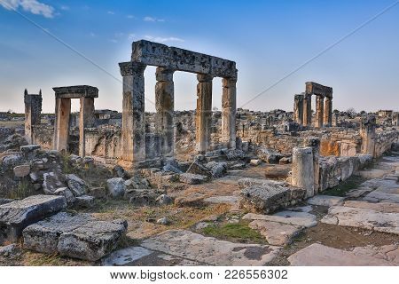 Ruins Of Appollo Temple With Fortress At Back In Ancient Corinth, Peloponnese, Greece.